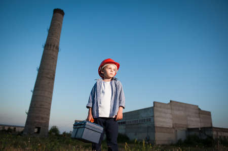 cute little boy in red helmet holding tool box on industry plant factory background on dusk with blue sky with copy space