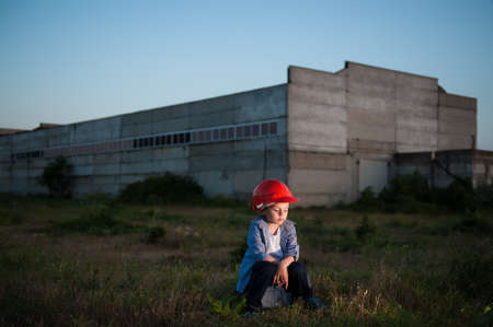 dismissal and unemployment concept of upset sad little boy red helmet sitting on tool box on idustry factory plant background