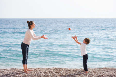 happy active young family of mother woman and offspring kid playing with apple on sea beach in spring time during leisure agility games with copy space