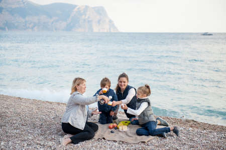 happy active family of mother grandmother and two kids drinking hot tea on sea coast with mountain on background with copy space during spring leisure vacation