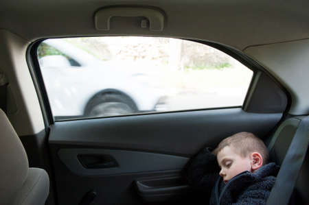 automotive concept of sleeping little kid with eyes closed inside car with window during travel trip