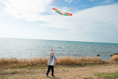 happy active little caucasian boy holding flying colorful kite standing on sea shore during summer leisure holiday