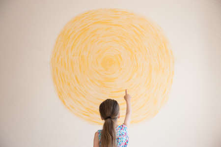 creative concept of little girl pointing finger at yellow circle sun painted on wall with copy space