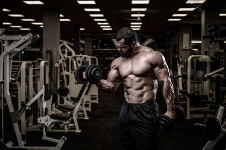 success concept of strong young male bearded athlete lifting heavy weight dumbbells in fitness sport gym