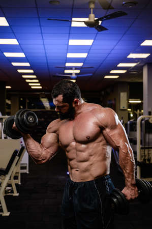 muscular bearded strong caucasian man lifting dumbbells during heavy workout train in sport gym