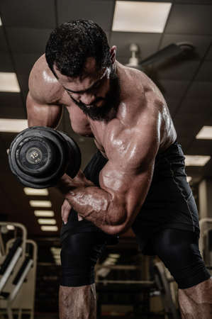 strong bearded young male training biceps muscle using heavy dumbbell in sport gym