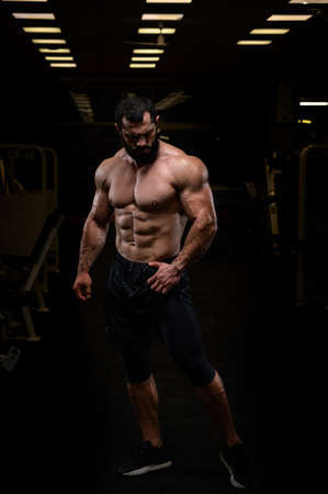 sport lifestyle of strong young athlete bearded caucasian man with perfect athletic physique body torso abdominal and chest muscle in dark fitness gym Stock Photo