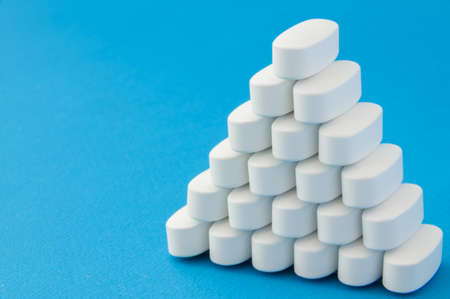 pharmacy production concept of many white tablets pills on blue surface with copy space
