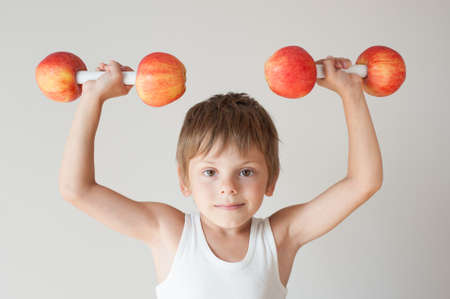 cute little boy in white tank top lifting dumbbells from fresh apples during sport training