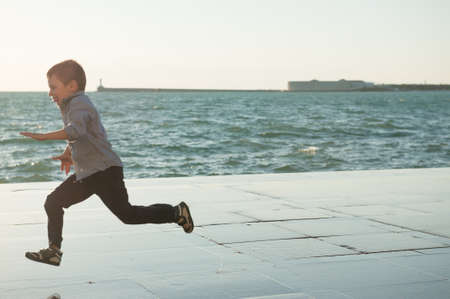 fast escape leisure concept of little active boy running away on sea seafront shore in city urban town