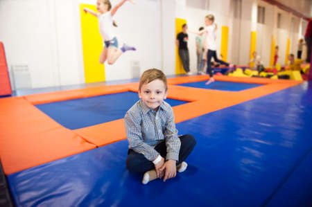 healthy little boy sitting on trampoline among jumping kids indoors in leisure activity club Stock Photo