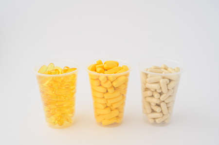 drugstore concept of three plastic cups with pills softgels omega3 capsule vitamins tablets on white background with copy space