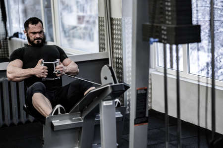 sport motivation workout concept of strong young man with beard lifting heavy weight in fitness gym preparing for contest