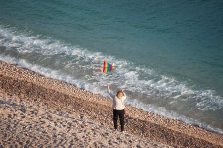 woman age emancipation concept of old female with flying colorful kite on sunset beautiful sea beach with waves of water and blowing wind in springtime