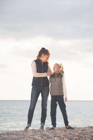 happy caucasian family of young mother woman hugging daughter wearing spring autumn fashion collection jacket on sea shore in sunset