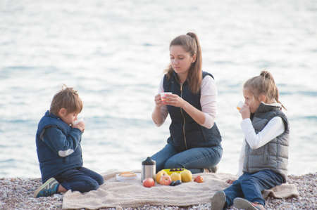 active caucasian sport family in sleeveless jackets sitting on sea beach during spring picnic drinking hot tea
