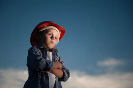 labor day in USA concept of pensive child in red helmet on dark night sky background with copy space Stock Photo