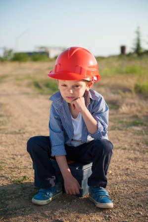 upset little kid in orange helmet sitting on road to factory industrial plant being fired