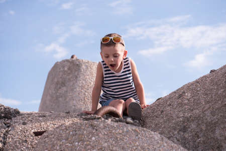 Little kid in a vest sits on the background of the sky Stock Photo