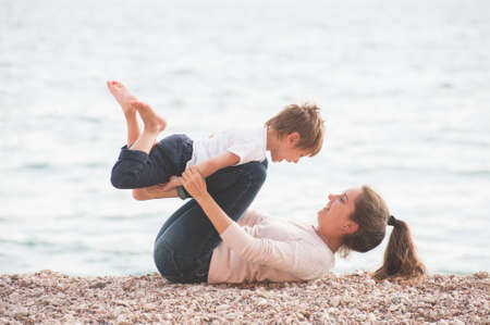 happy delightful family of playful adorable mother and laughing child on sea beach during summer vacation holiday leisure games