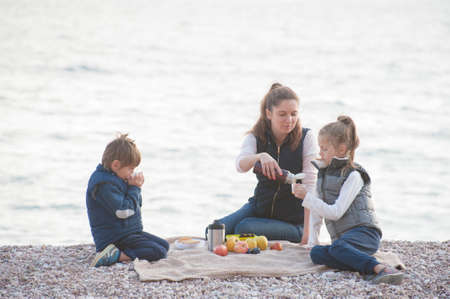 active caucasian family in sleeveless jacket sitting on sea beach drinking hot tea during outdoor leisure vacation travel Stock Photo