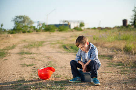 lonely lost upset kid worker sitting on toolbox on road to industrial factory with lying orange helmet