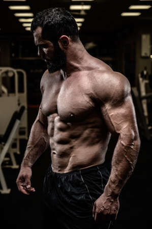 strong young bearded caucasian man with sport physique body torso standing in dark fitness gym with equipment Stock Photo