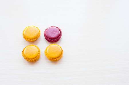 four different-colored round French macaron cookies on the table with copy space Stock Photo