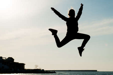 leisure activity of happy young kid jumping in air in city with sea on sunset