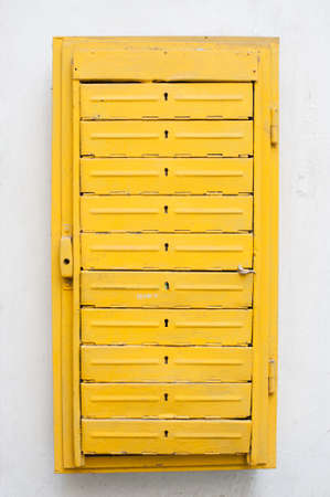 mail concept old vintage yellow iron letterbox with keyholes on white wall