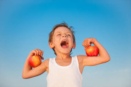 strong little kid in white tank top showing muscles with fresh apple on arms with blue sky background with copy space Stock Photo