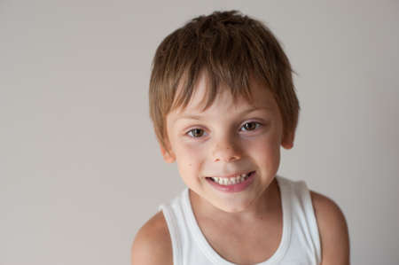 delightful happy smiling little kid in tank top on background with copy space