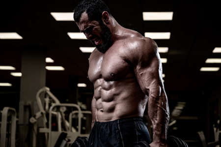 heavy training of bearded man in sport gym pumping iron with effort
