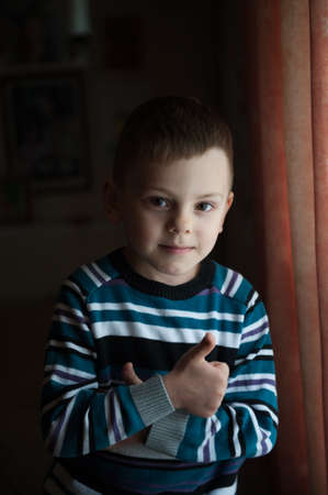 one little caucasian smiling boy in sweater showing thumbs up near indoors window Stock Photo