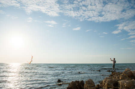 one active male playing with flying kite standing on sea rocky coast on sunset summer leisure activity Stock Photo