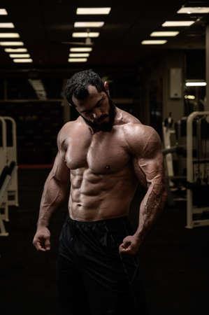 muscular bearded man in sport bodybuilding night fitness club gym