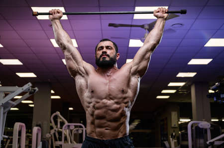 strong young bearded male during stretching with bar in gym Stock Photo
