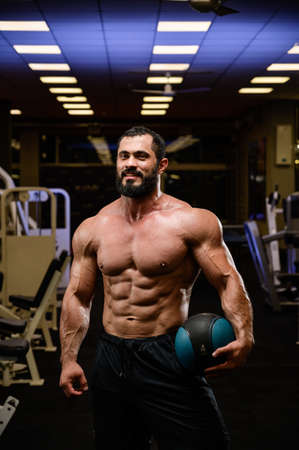 happy smiling strong young bearded athlete with medicine heavy ball in blue lit night sport gym Stock Photo