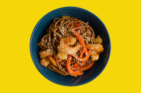 wok noodles pasta asian food with shrimp in blue dish on yellow isolated background