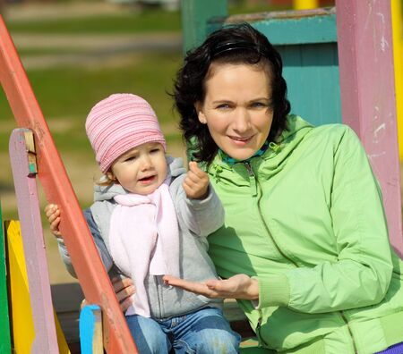 Mother and little child playing on the playground outdoors on a sunny day photo