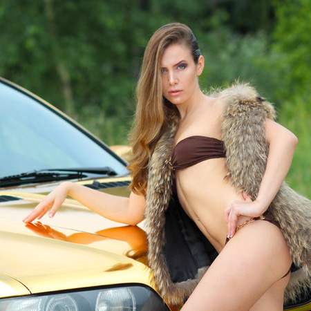 Beautiful sexy girl in bikini and in fur cape posing on a background of golden car. sexy lady near the golden car.  photo