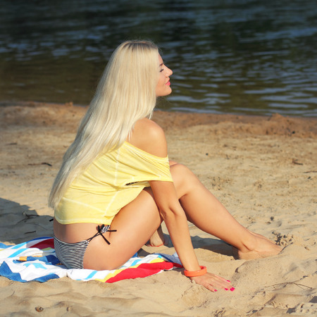 portrait of a beautiful girl in yellow t-shirt on the beach photo