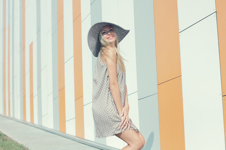 hollow wall: beautiful happy girl in a bright dress and a long hollow hat having fun near the orange wall