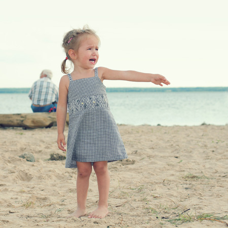 offended crying little girl on the beach. sad little girl with blond hair Stock Photo