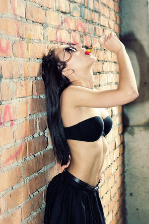 sucking lollipop: Young sensual girl sucking lollipop on the background of old brick wall. Outdoors, lifestyle. Stock Photo