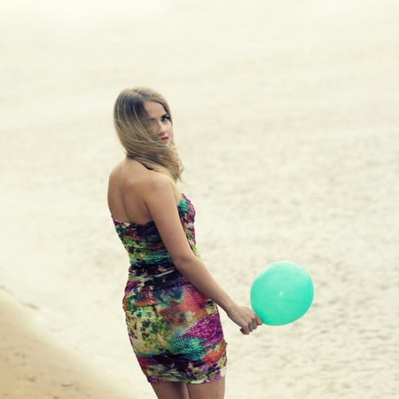 Happy young woman having fun with colorful latex balloon on water background. photo