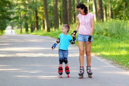 mother and son learn to roller skate. Mom with child having fun on roller skates photo