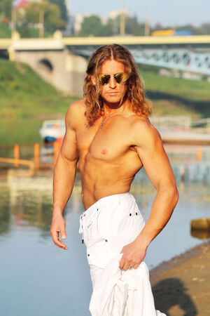 seminude: seminude sexy caucasian fit man in sunglasses posing on the beach in the city