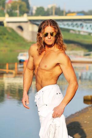 seminude: sexy seminude caucasico rientra in occhiali da sole in posa sulla spiaggia in citt�