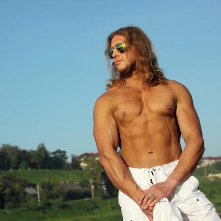 seminude: sexy seminude caucasico in forma l'uomo in occhiali da sole in posa sulla spiaggia in citt�